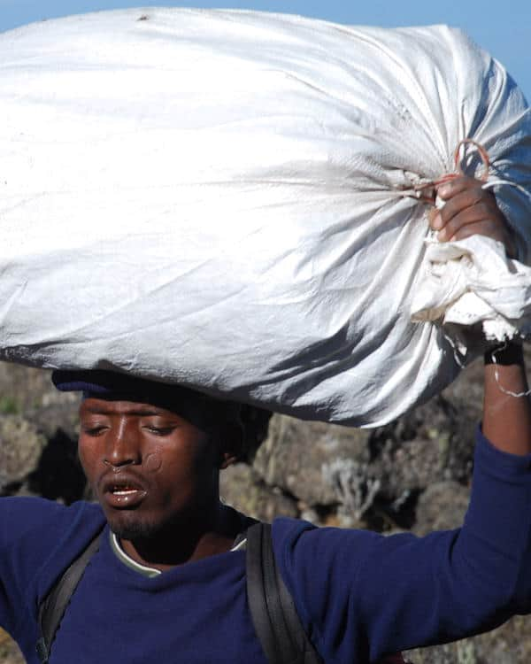 Porter carries large white rice sack on his head on Machame Route