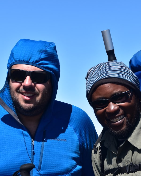 Kilimanjaro guide Joshua and trekker both in sunglasses smile for the camera under a blue sky