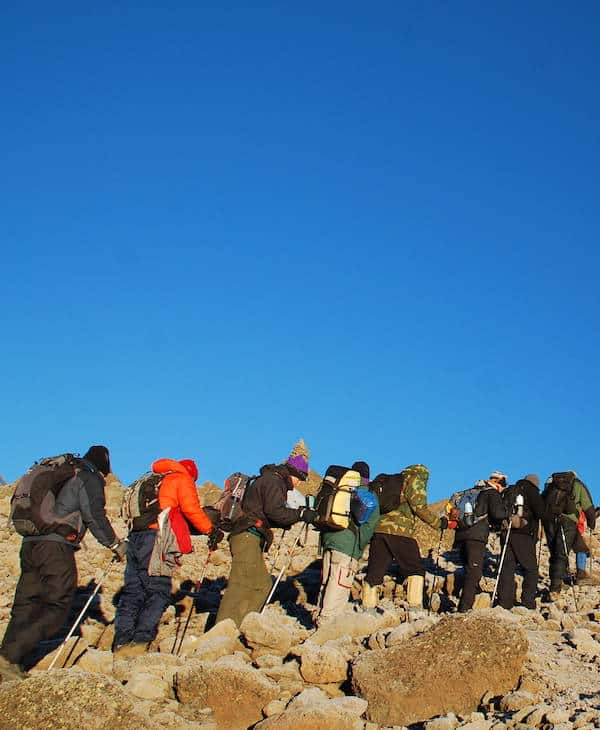 Line of trekkers parade up the slopes of Kibo under a clear deep blue sky