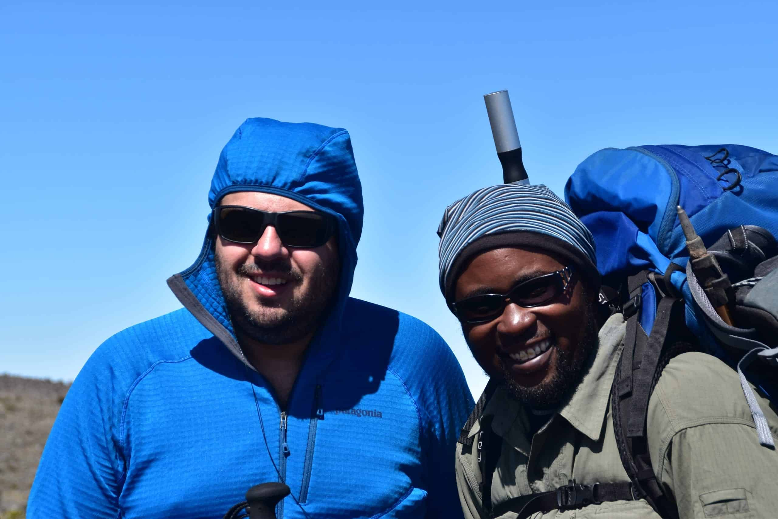 Kilimanjaro Experts dirtector Joshua Ruhimbi and trekker on the mountain