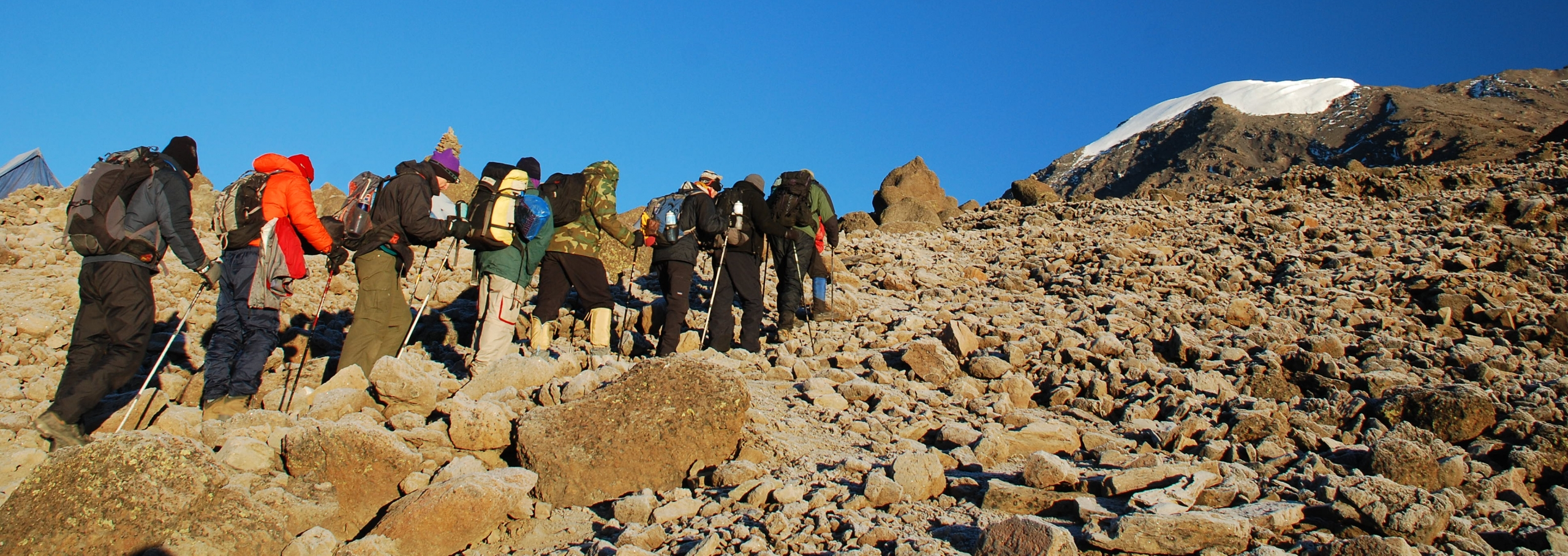A line of trekkers slowly making their way up towards Rebmann Glacier on Kilimanjaro against a vivid blue sky