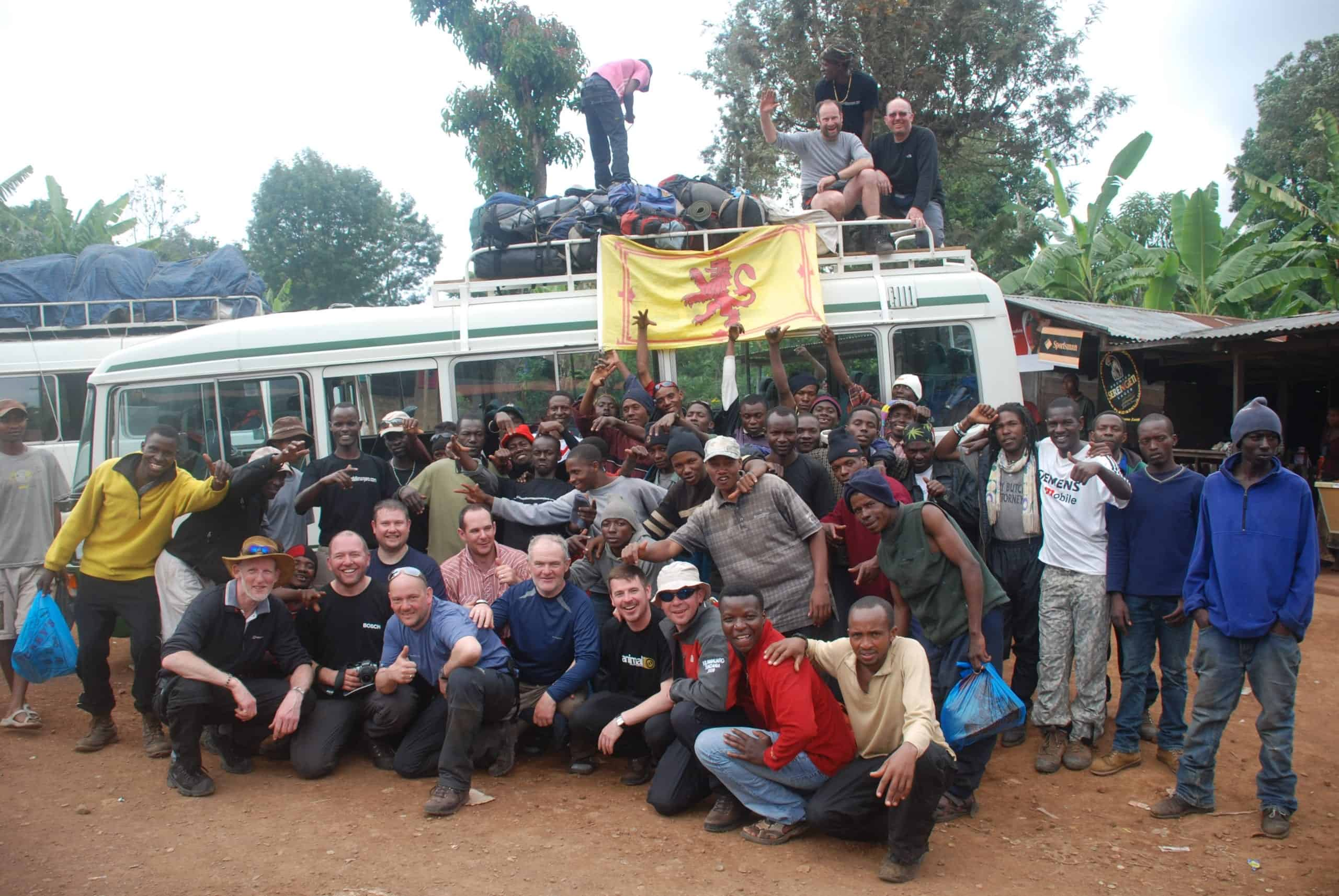 Large crowd of trekkers and porters in front of their coach at the end of their successful trek with Scottish flag draped from bus roof rack