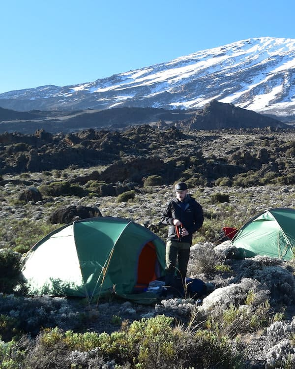 trekker stands outside green tent with Kili's snowy Kibo summit in the background
