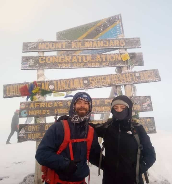 Two trekkers posing in front of Kilimanjaro's summit sign in snowy conditions