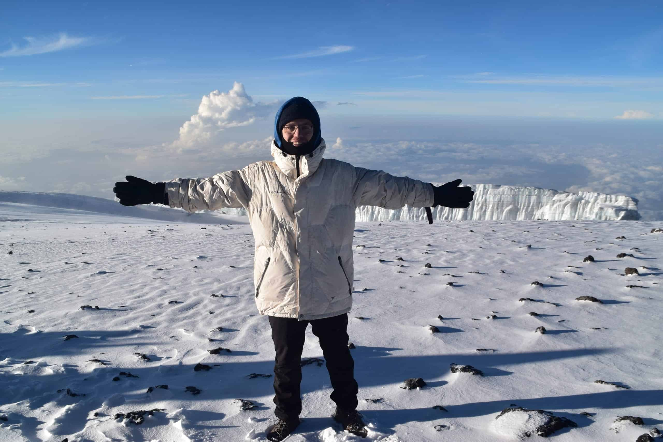 Lone trekker in a large white coat with arms out wide on front of a glacier on the summit of Kilimanjaro