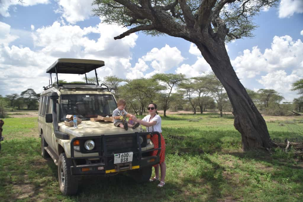 Mum stands by safari vehicle with the top popped up, while toddler sits on the bonnet eating his lunch