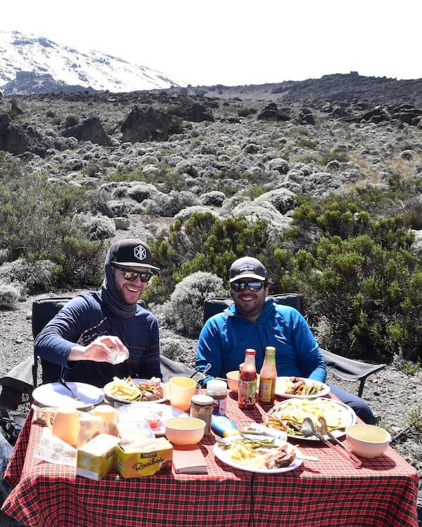 Two smiling trekkers tuck into an al-fresco breakfast on Kilimanjaro