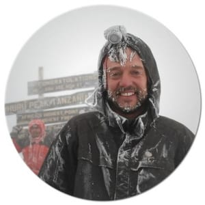 Kilimanjaro Expert's director and guide book author Henry Stedman at the top of Kilimanjaro with beard and hair frosted with snow
