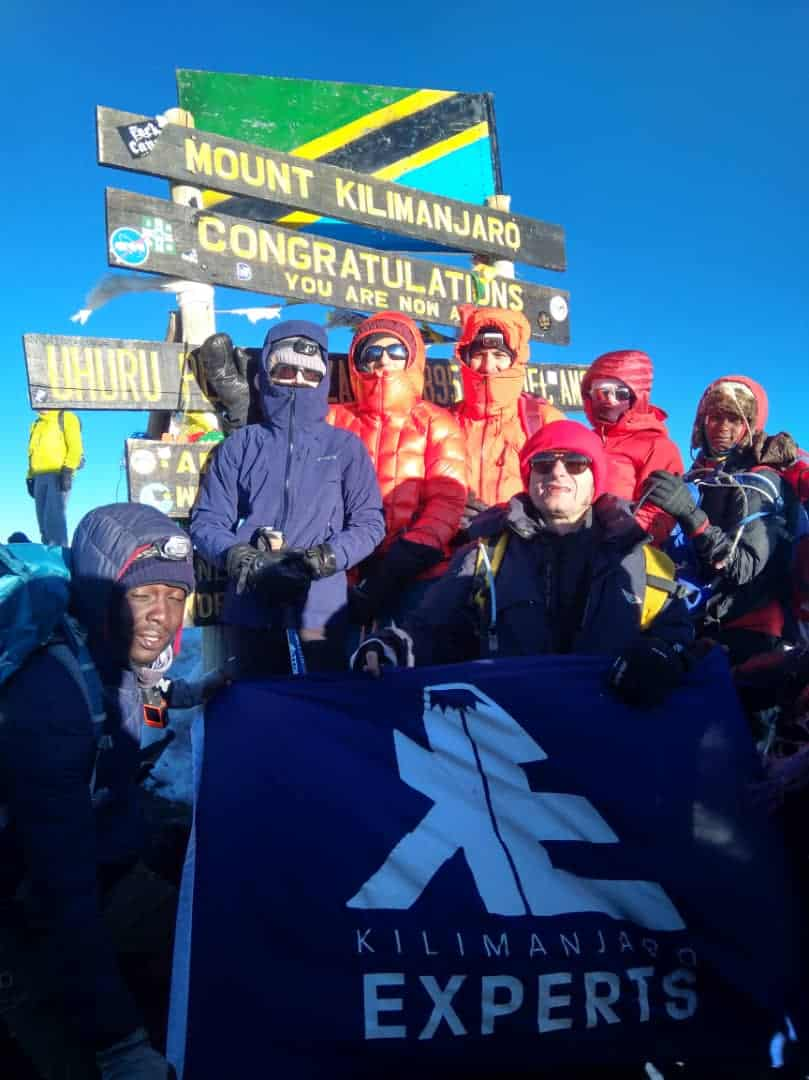 Group of Kilimanjaro trekkers at the summit with Kilimanjaro Experts flag