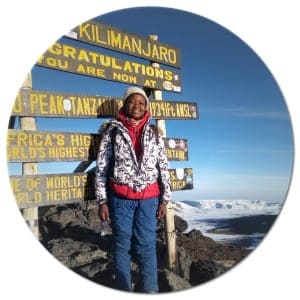 Kilimanjaro Expert's guide Janeth in front of the signboard at Kilimanjaro's Uhuru Peak