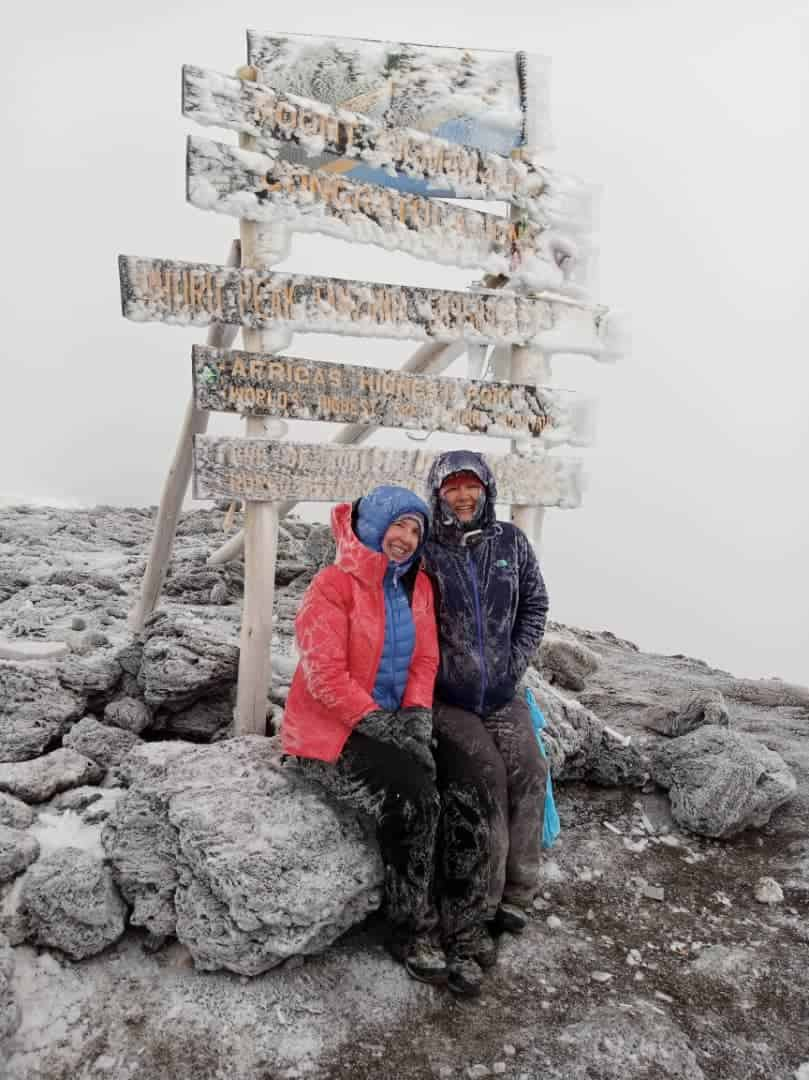 Two trekkers shiver at Kilimanjaro's summit sign all frosted in snow