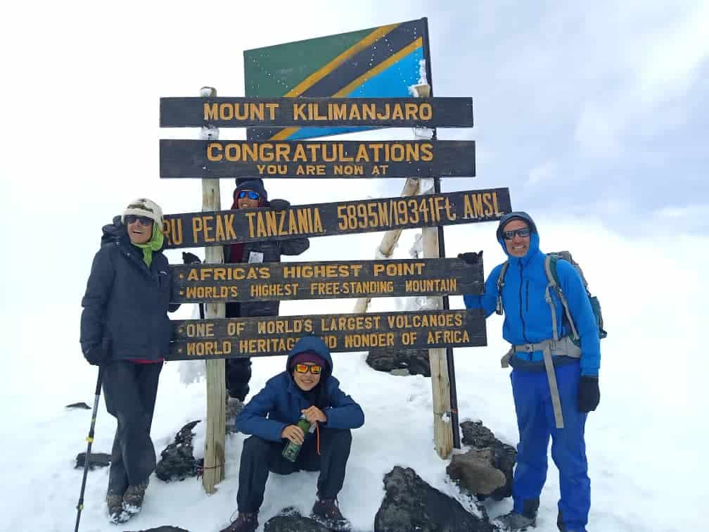 Four trekkers pose around Kilimanjaro's summit sign