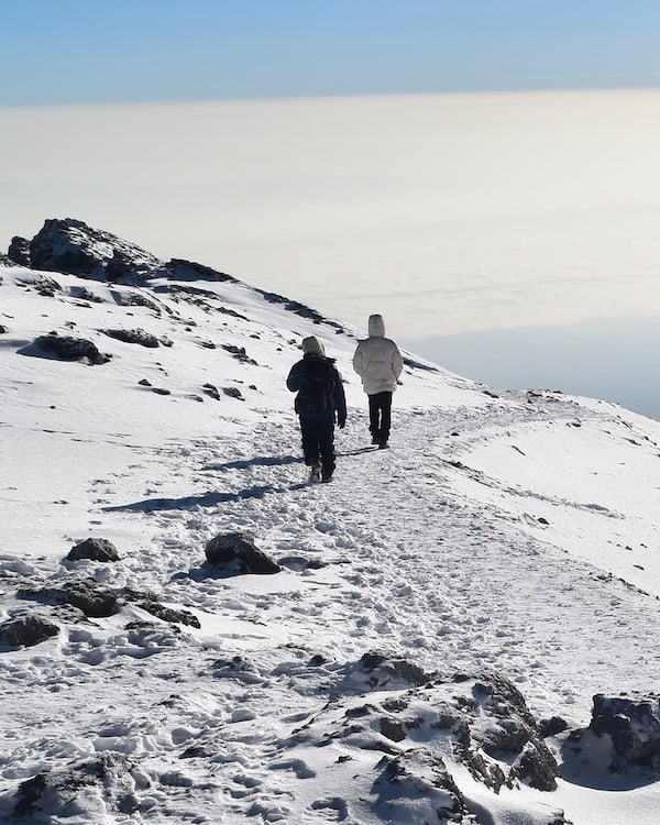 Two trekkers saunter through the snow on Kilimanjaro's crater rim